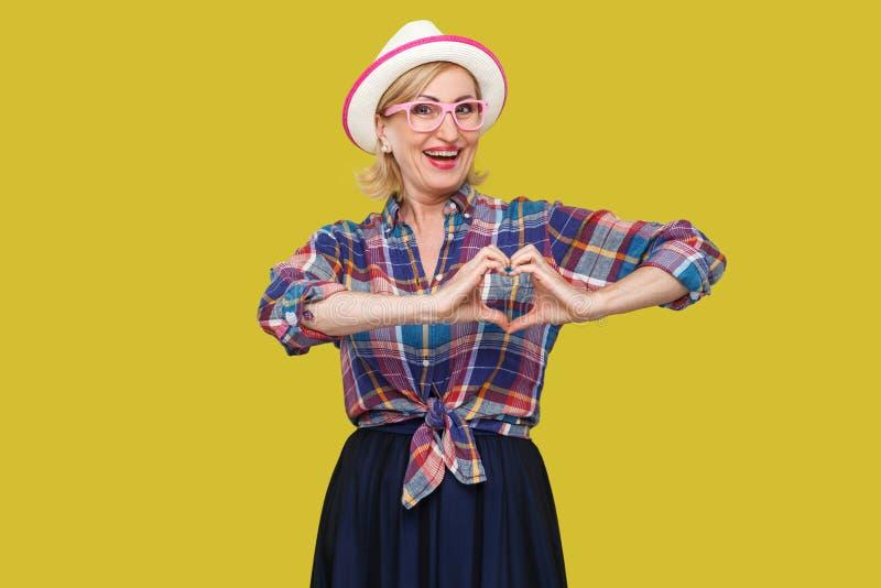 Porträt der glücklichen ruhigen modernen stilvollen reifen Frau in der zufälligen Art mit weißer Hutstellung mit Handherz-Formges lizenzfreie stockbilder