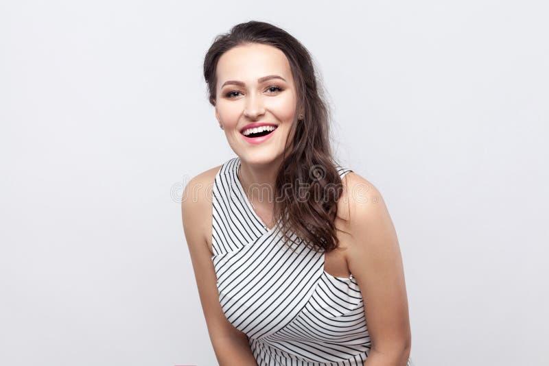 Porträt der glücklichen schönen jungen brunette Frau mit Make-up und gestreifter Kleiderstellung und dem Betrachten der Kamera mi lizenzfreies stockfoto