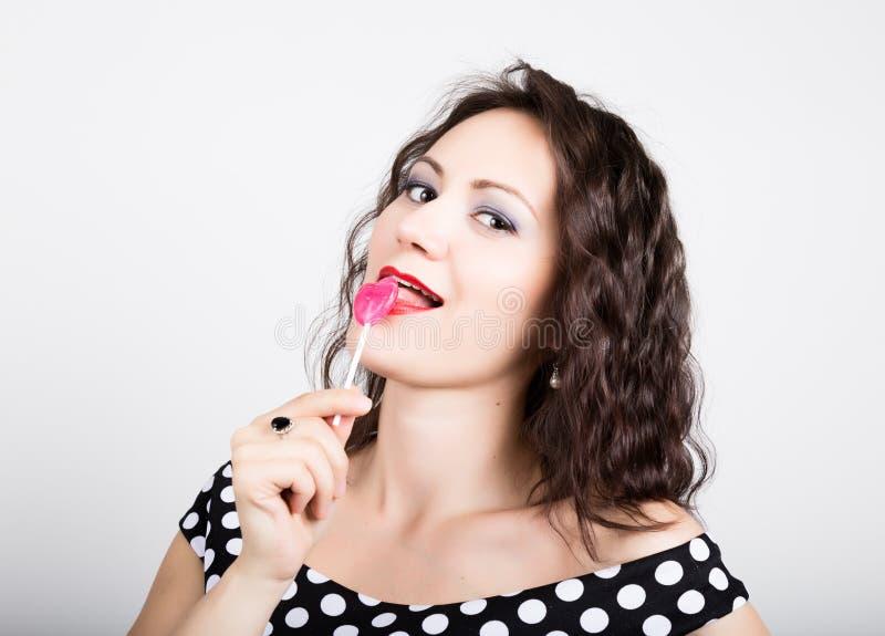 Porträt der glücklichen schönen jungen Frau, die chupa chups leckt hübsche Frau mit geformtem Lutscher des Herzens lizenzfreies stockbild