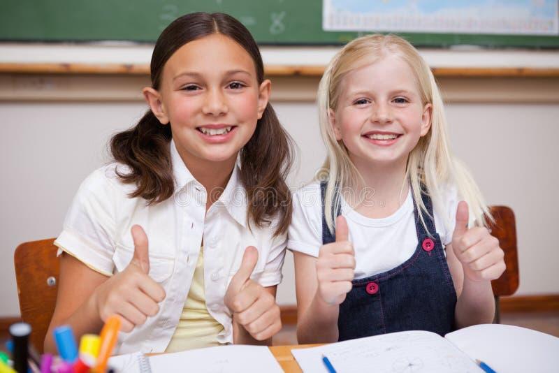 Porträt der glücklichen Schüler, die oben zusammen mit den Daumen arbeiten stockbilder