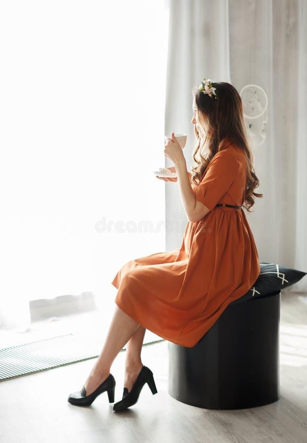 Porträt der glücklichen schwangeren Frau in einem Kleid mit dem trinkenden Tee der Schale, der zu Hause durch Fenster schaut Das  stockfotografie