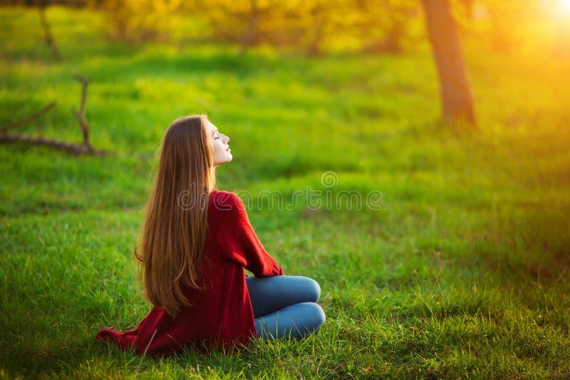 Porträt der glücklichen sportlichen Frau, die im Park auf grüner Wiese sich entspannt Frohes weibliches Modell, das draußen Frisc lizenzfreie stockfotografie