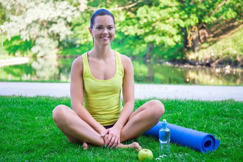 Porträt der glücklichen sportlichen Frau, die mit Yogamatte und Wasser I sitzt lizenzfreie stockfotografie