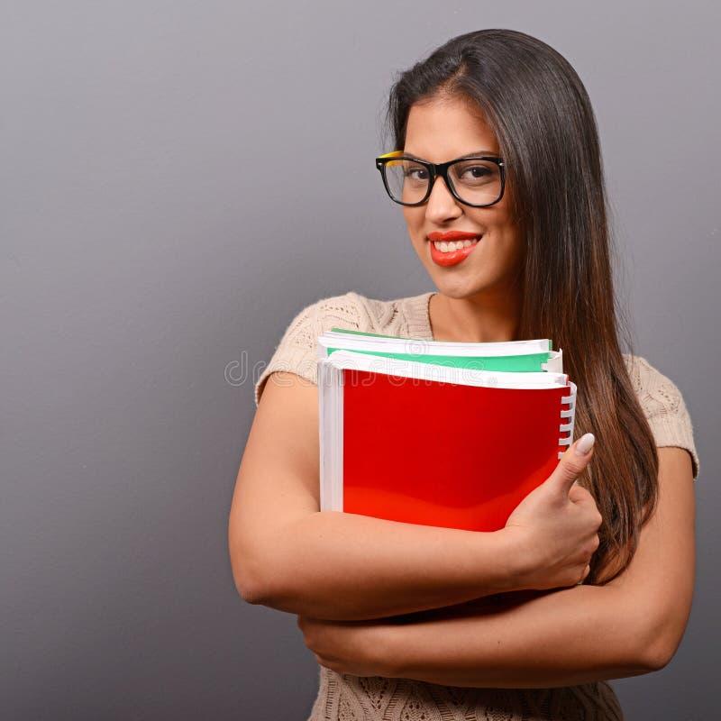 Porträt der glücklichen Studentenfrau, die Bücher mit dem Daumen oben gegen grauen Hintergrund hält stockfotografie