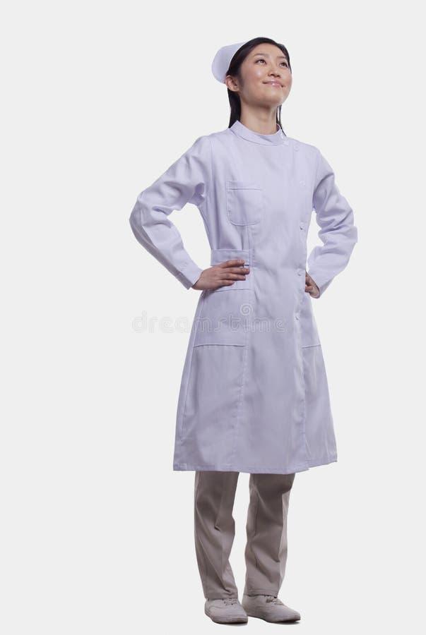 Porträt der glücklichen weiblichen Krankenschwester in der Uniform mit den Händen auf Hüften, Atelieraufnahme, in voller Länge lizenzfreie stockbilder