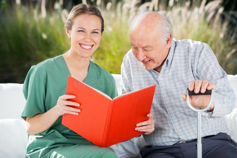 Porträt der glücklichen weiblichen Krankenschwester Reading Book For stockfotografie