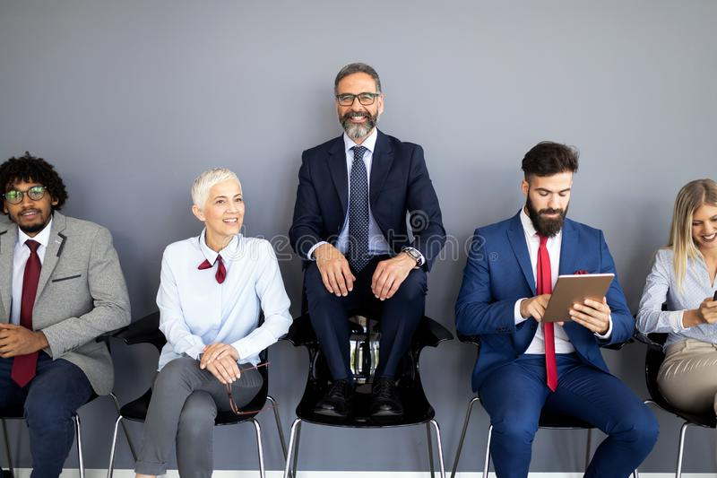 Porträt der Gruppe verschiedener Unternehmenskollegen, die in Folge zusammen an einem Tisch in einem hellen modernen Büro stehen stockbild
