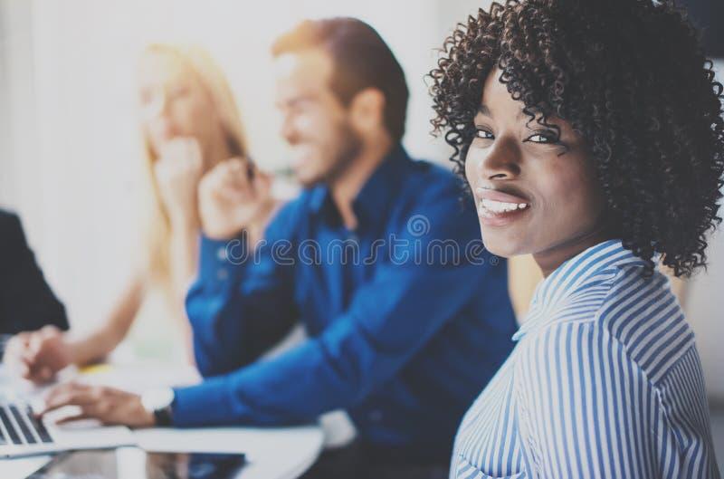Porträt der hübschen AfroamerikanerGeschäftsfrau mit dem Afrolächeln an der Kamera Coworking-Team im Brainstorming lizenzfreies stockbild