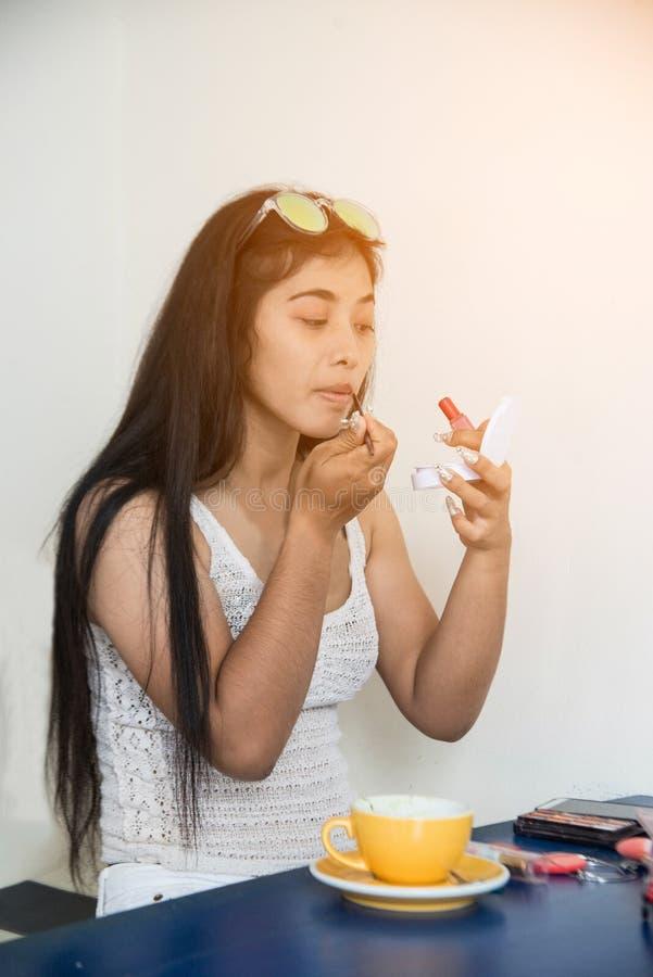 Porträt der hübschen Asiatin wendet roten Lippenstift an Hand des Make-upmeisters, malende Lippen der jungen Schönheitsmodellfrau lizenzfreie stockfotografie