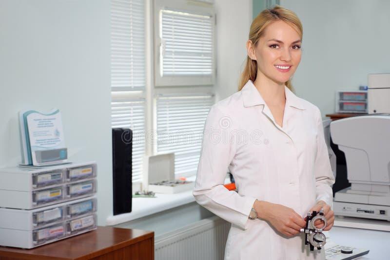 Porträt der hübschen Augenarztstellung mit ophthalmologic Gerät im Kabinett stockbild