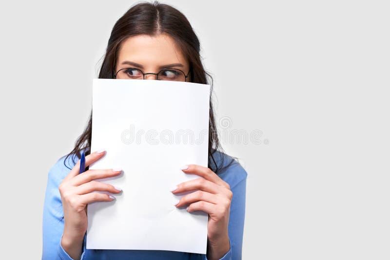Porträt der hübschen brunette jungen Studentin, die blaue Bluse und runde transparente Brillen, versteckend mit Weißbuch trägt stockfoto