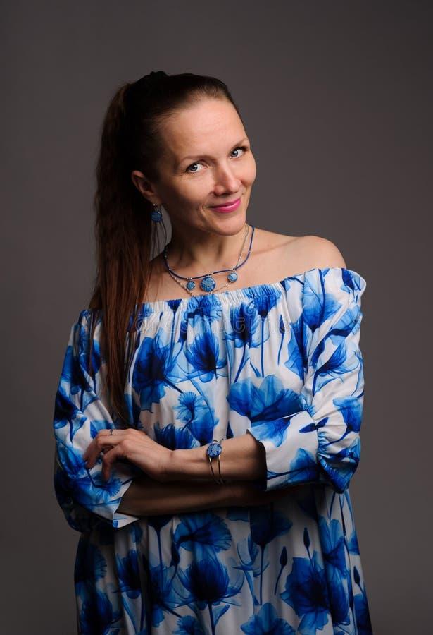Porträt der hübschen Frau im blauen Kleid über blauem Hintergrund stockbilder