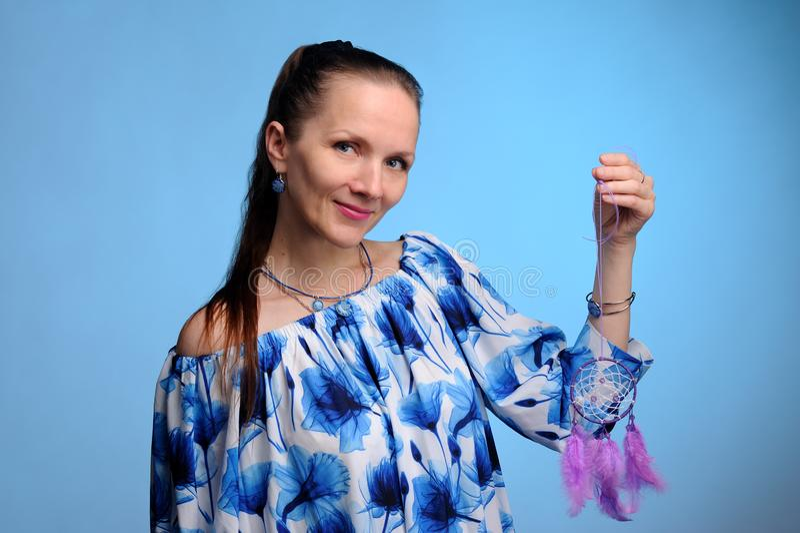 Porträt der hübschen Frau im blauen Kleid über blauem Hintergrund lizenzfreies stockbild