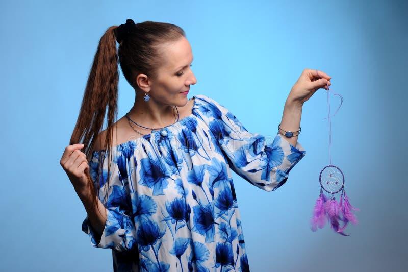 Porträt der hübschen Frau im blauen Kleid über blauem Hintergrund stockfoto