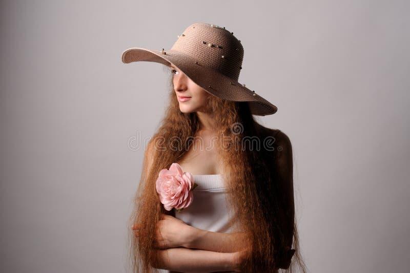 Porträt der hübschen Frau im rosa Hut lizenzfreie stockbilder