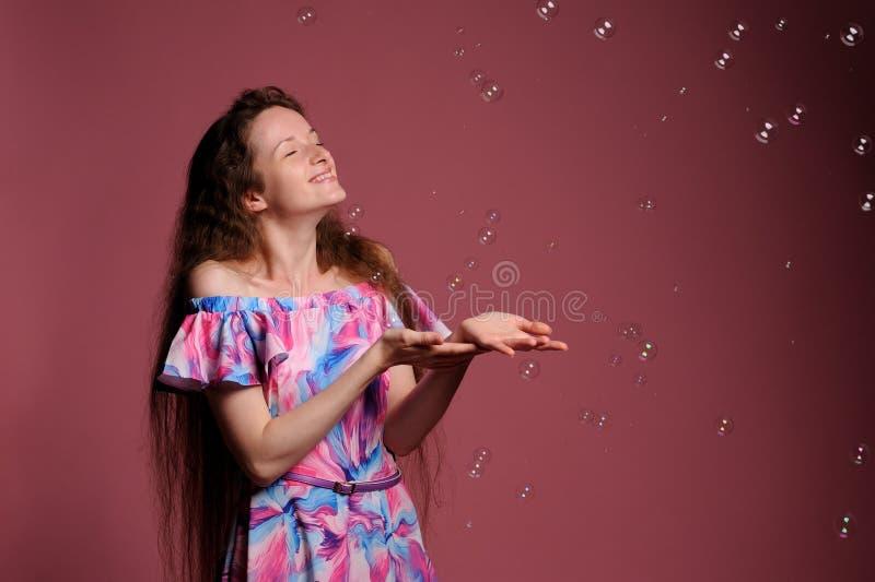 Porträt der hübschen Frau im rosa Kleid stockfotografie