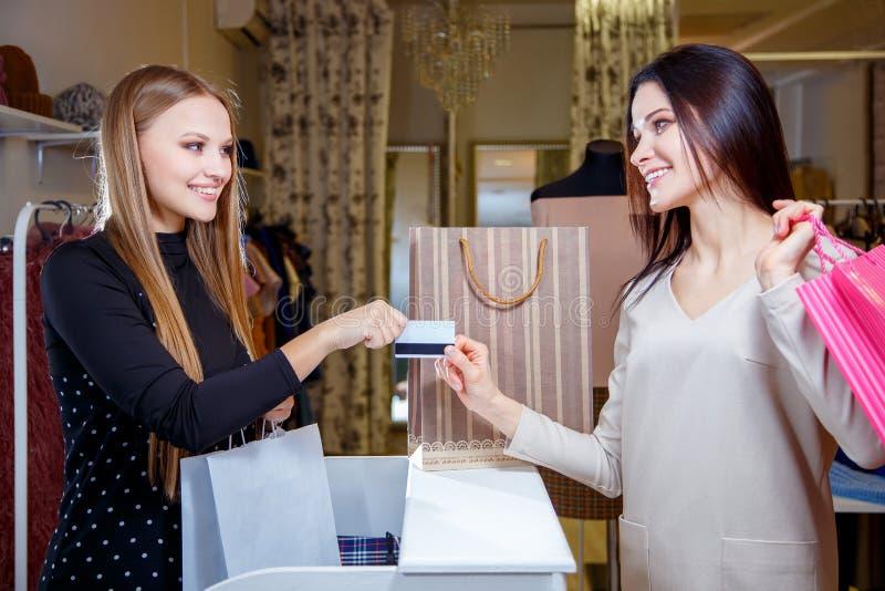 Porträt der hübschen Frau Kreditkarte beim Zahlen gebend dem Verkäufer für ihren Kauf stockfotografie