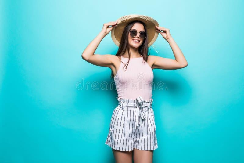 Porträt der hübschen Frau in der Sonnenbrille und im Hut über blauem buntem Seashells gestalten auf Sandhintergrund lizenzfreie stockfotografie