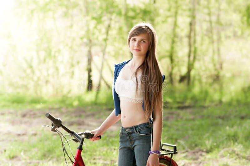 Porträt der hübschen Jugendlichen mit Fahrrad stockbild