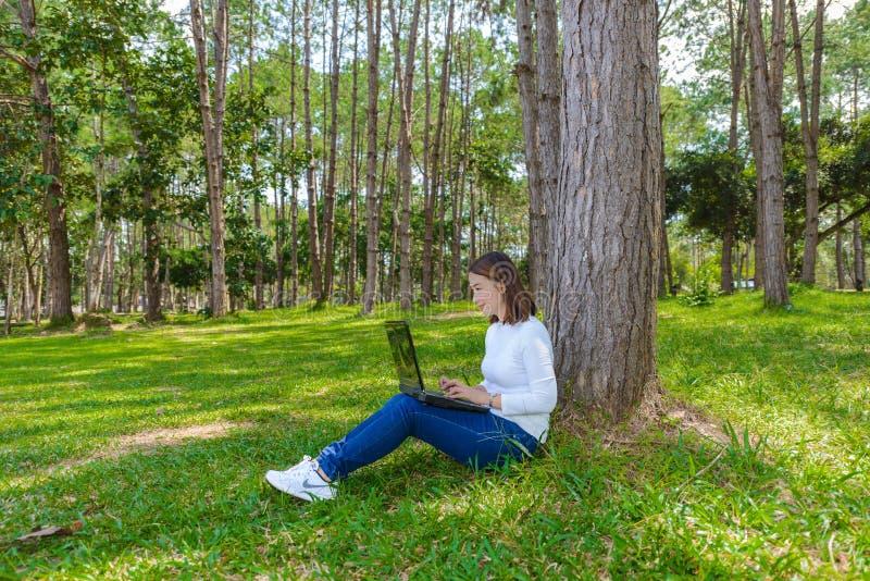 Porträt der hübschen jungen Frau, die auf grünem Gras im Park SU sitzt lizenzfreie stockbilder