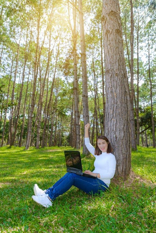 Porträt der hübschen jungen Frau, die auf grünem Gras im Park SU sitzt stockfotografie