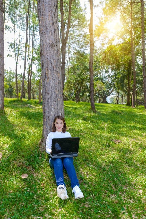 Porträt der hübschen jungen Frau, die auf grünem Gras im Park SU sitzt lizenzfreie stockfotos