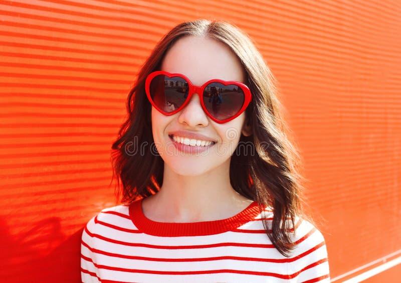 Porträt der hübschen lächelnden Frau in der roten Sonnenbrille stockfoto