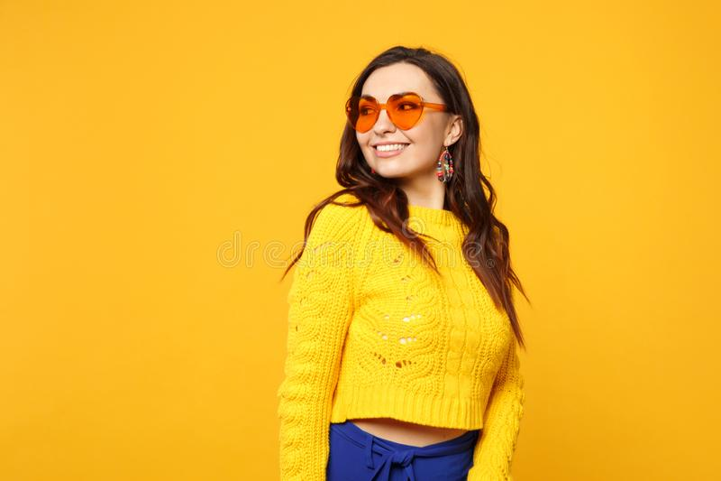 Porträt der hübschen lächelnden jungen Frau in der Strickjacke, blaue Hose, Herzgläser, die beiseite auf gelb-orangeem lokalisier lizenzfreie stockbilder