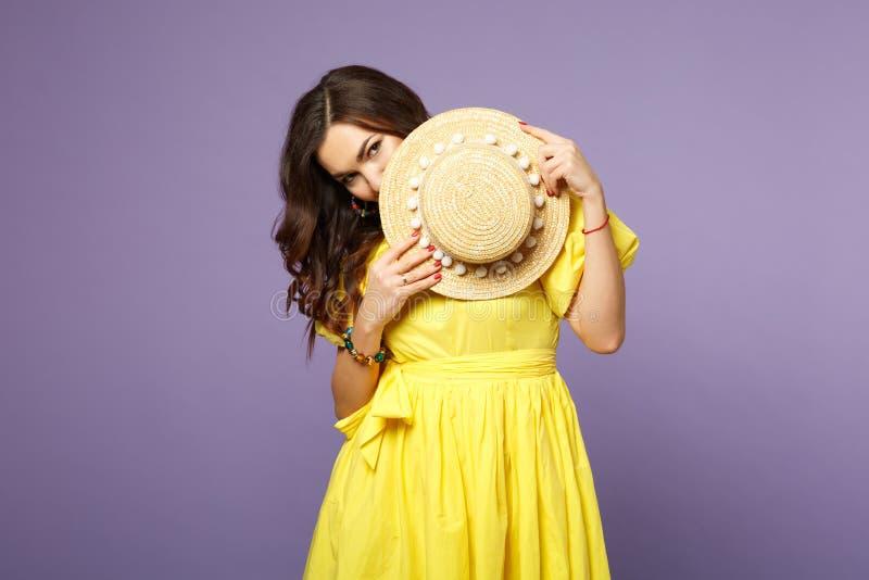 Porträt der hübschen verwirrten jungen Frau im gelben Kleiderbedeckungsgesicht mit dem Sommerhut lokalisiert auf Pastellveilchen stockbild