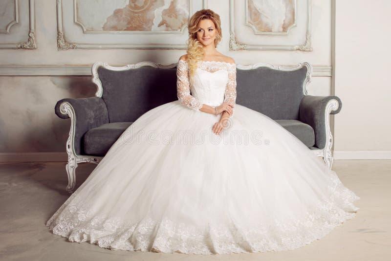 Porträt der hübscher Frau im Hochzeitskleid Die Mädchenbraut sitzt in einem Stuhl lizenzfreie stockfotografie