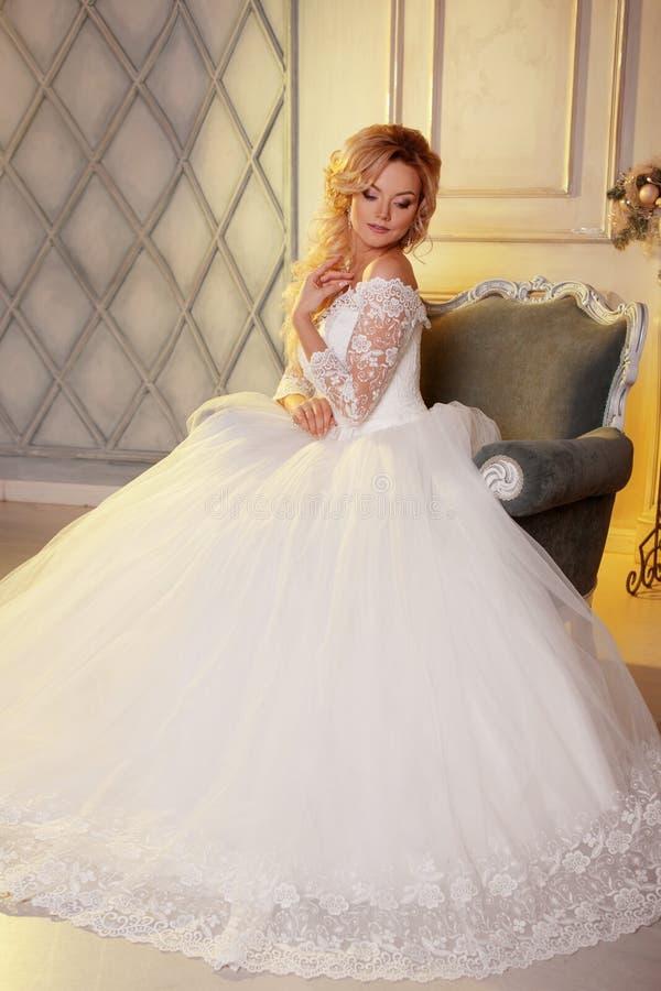 Porträt der hübscher Frau im Hochzeitskleid Die Mädchenbraut sitzt in einem Stuhl lizenzfreies stockbild