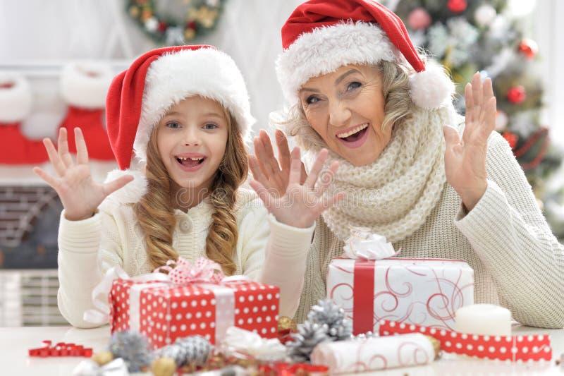 Porträt der herausgenommenen Großmutter und ihrer kleinen netten Enkelin mit Weihnachtsgeschenk lizenzfreie stockbilder
