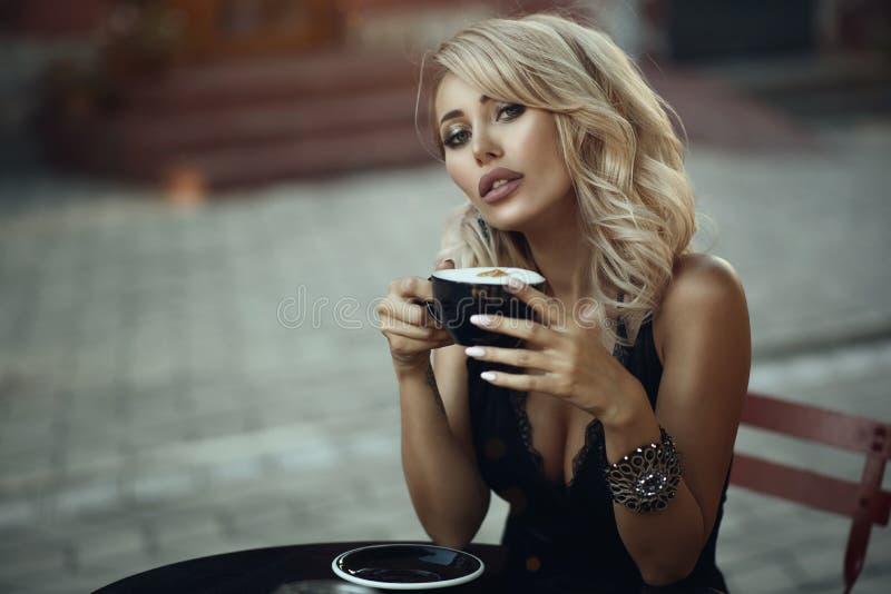 Porträt der herrlichen eleganten blonden Frau, die am Tisch im netten Straßencafé hält eine Schale mit schaumigem Latte sitzt lizenzfreies stockfoto