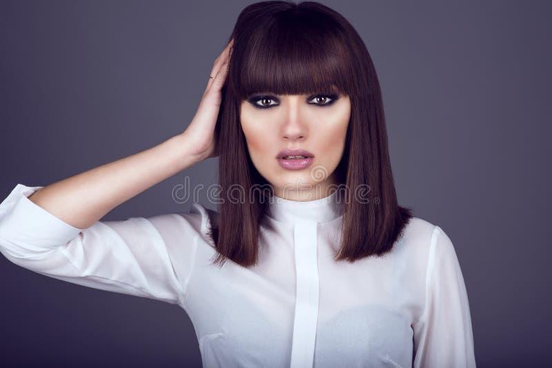 Porträt der herrlichen jungen dunkelhaarigen schauenden Frau gerades und rührendes Haar mit ihrer Hand lizenzfreies stockfoto