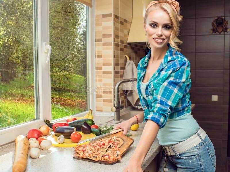 Porträt der herrlichen lächelnden blonden Hausfrau, die frisch gekochte Schnittpizza auf Brotschneidebrett zeigt lizenzfreie stockfotografie