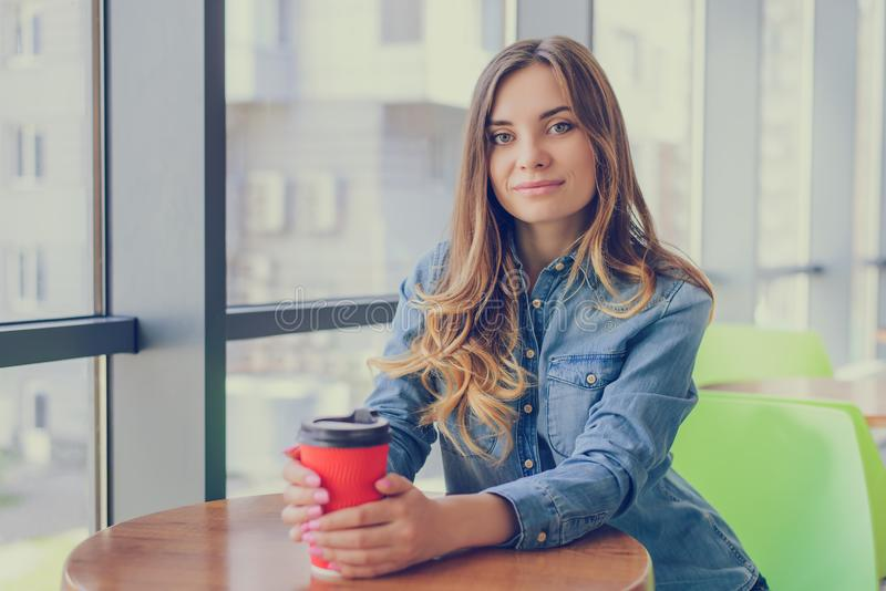 Porträt der herrlichen lächelnden jungen Frau, die Mitnehmer-coffe trinkt lizenzfreie stockfotos