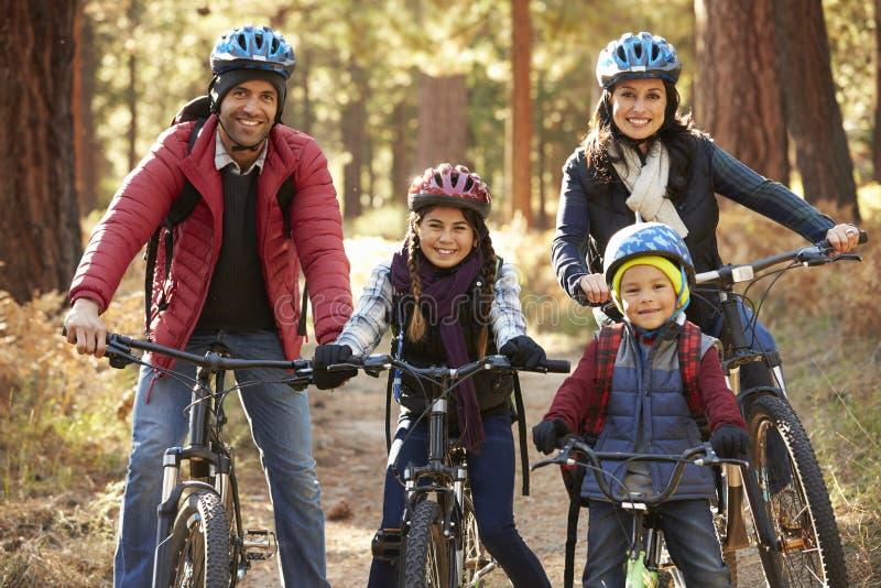 Porträt der hispanischen Familie auf Fahrrädern in einem Wald stockbild