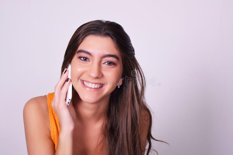 Porträt der hispanischen/kaukasischen jungen Frau, die ein bewegliches Phon verwendet stockbild