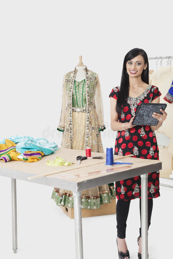 Porträt der indischen weiblichen Damenschneiderin am Designstudio stockfotos