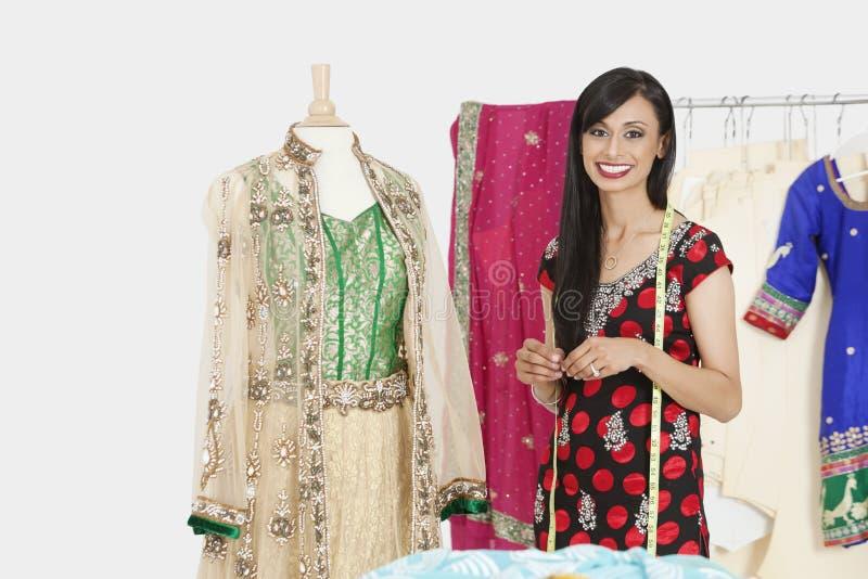 Porträt der indischen weiblichen Damenschneiderin, die eine Attrappe bereitsteht, kleidete in der traditionellen Abnutzung an lizenzfreies stockbild