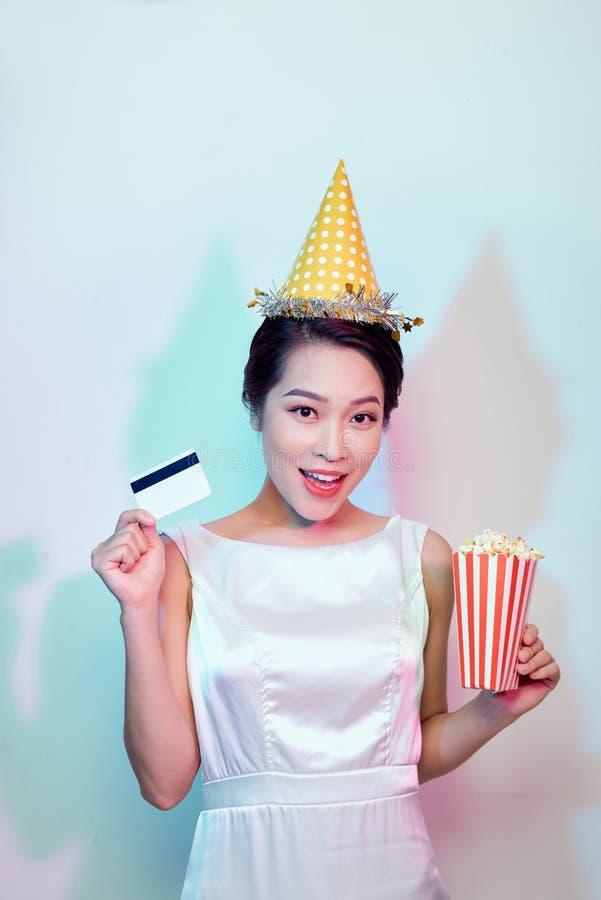 Porträt der jungen überglücklichen attraktiven Frau in weißes Kleideraufpassendem Film, Eimer des Popcorns und der Kreditkarte ha lizenzfreie stockfotos