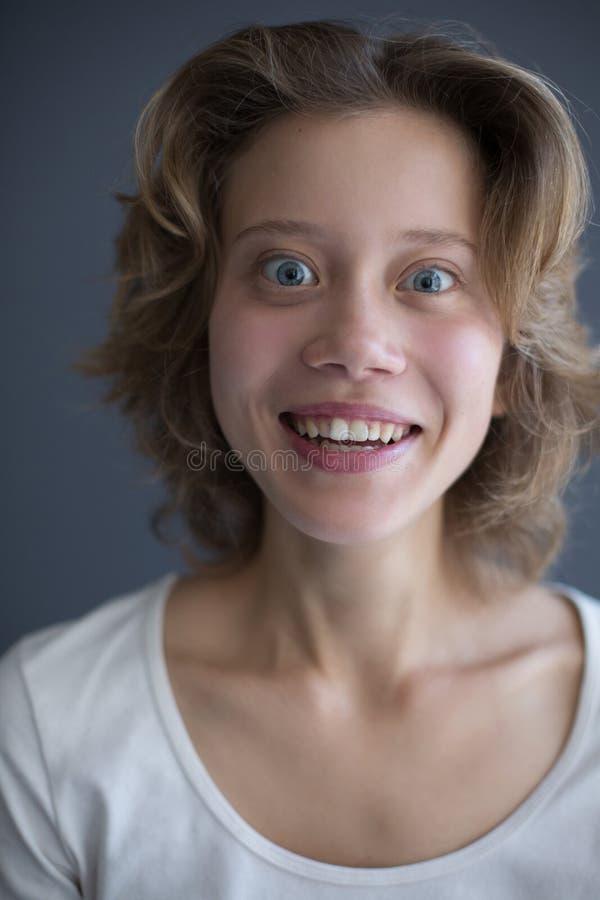 Porträt der jungen überraschten Frau, die froh in camera schaut stockbilder