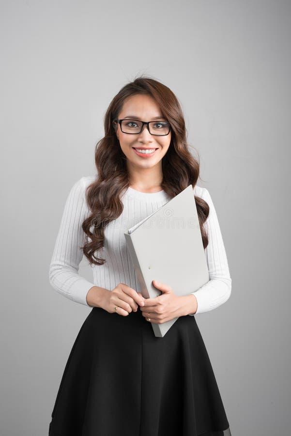 Porträt der jungen überzeugten asiatischen Geschäftsfrau mit Ordner stockbilder