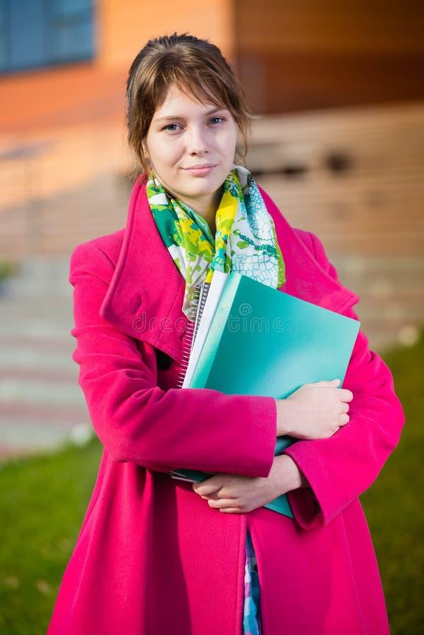 Porträt der jungen anziehenden Frau, die Bildung hält stockfotos