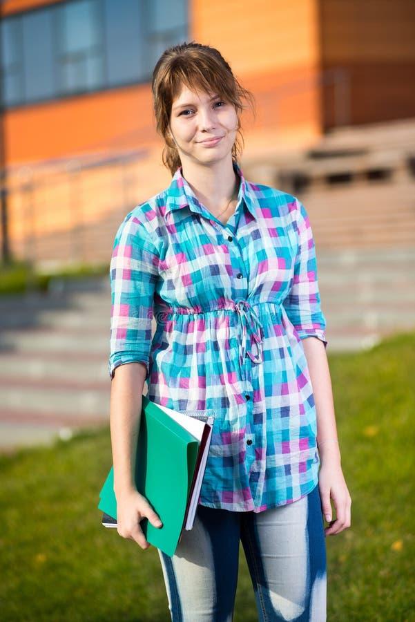 Porträt der jungen anziehenden Frau, die Bildung hält stockbilder