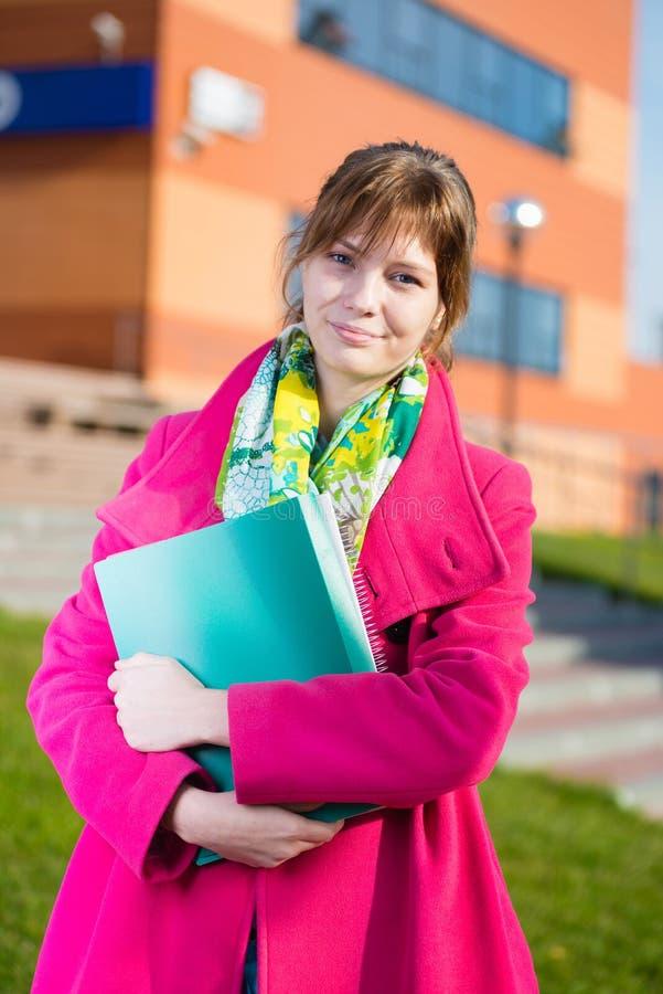 Porträt der jungen anziehenden Frau, die Bildung hält stockfoto