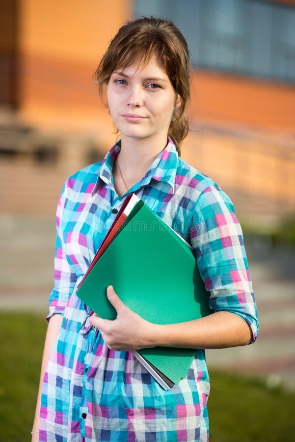 Porträt der jungen anziehenden Frau, die Bildung hält stockfotografie