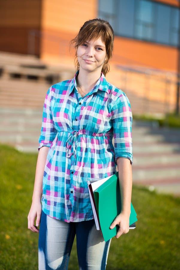 Porträt der jungen anziehenden Frau, die Bildung hält, bucht Schließen Sie herauf Schuß stockfotografie