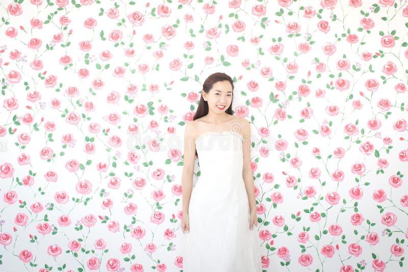 Porträt der jungen asiatischen Braut, die an der Kamera, rosa Rosen lächelt und lizenzfreie stockbilder