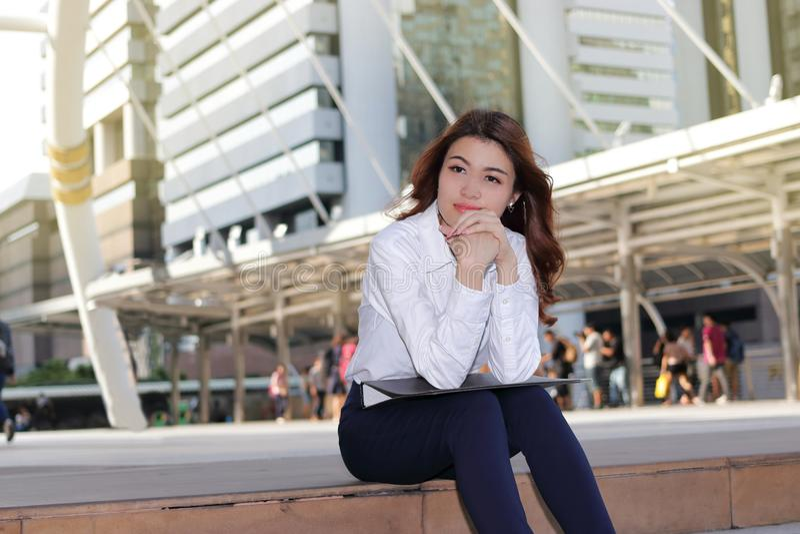Porträt der jungen asiatischen Geschäftsfrau des Führers, die auf Treppenhaus im städtischen Gebäudehintergrund denkt und sitzt stockfoto